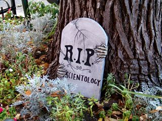 """""""R.I.P. Scientology"""" on a fake tombstone placed in a small garden directly in front of the entrance to the Founding Org."""