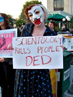 """In keeping with the """"undead"""" theme, Beret holds a sign saying, """"Scientology kills people DED (sic)""""."""