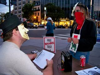 """""""Free Brains Test"""" in action. The """"preclear"""" holds the cylinders on our faux E-meter, while the """"auditor"""" asks questions of the preclear. The photo at right illustrates the final step in the Free Brains Test, where he asks, """"May I feel your brain?"""" and then feels the preclear's brain."""