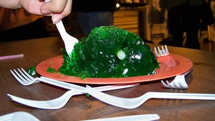 A person takes a piece of the gelatin mold shaped to look like a brain.