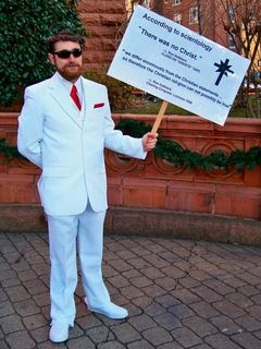 """John McNonymous dressed in a white suit and held sign saying, """"According to Scientology, 'There was no Christ,'"""" attributed to Scientology founder L. Ron Hubbard. The sign also quotes a 1958 lecture where Hubbard stated that, """"we differ enormously from the Christian statements ... so therefore the Christian religion cannot possibly be true."""""""