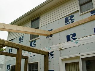 Up high, the roof over the porch begins to take form, as a horizontal beam is attached to the wall.