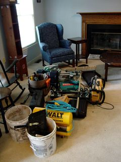In the living room, before work began in there, the workers used the space to keep their unused tools.