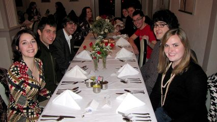 The wedding party is all smiles at the beginning of the rehearsal dinner.