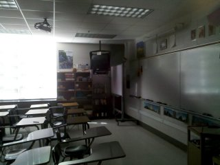 """In my time at SDHS, this was Room 3, the original """"IBM Lab"""", as it was called. When the computer lab was originally installed in 1995, it had three rows of one-piece IBM EduQuest computers. These were upgraded in 1997 to the IBM PC 300GL. Now, as Room 29, the same space again a typical SDHS classroom, now as Laura Stump's French classroom. From what I could tell, most classrooms have their original doors, windows, and HVAC units under the window. However, the lighting is different, the chalkboards are now dry erase boards (guessing that this is just a retrofit over the old chalkboard), and a ceiling-mounted digital projector is now present. The ceiling-mounted television is left over from this room's time as a computer lab, but from what I could tell, most classrooms now have a mounted television set."""