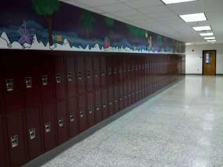 This is the new face of the locker area in the front of the school. I had my locker in this area (students generally kept the same locker for all four years at that time). The lockers had previously been arranged in rows perpendicular to the corridor (see file photo of the old lockers). This was no longer possible with the renovation, because a new, somewhat narrow room had been constructed in the space where these rows of lockers previously were, and thus the new lockers had to be mounted flat against the wall. The door to former Room 10 (Mrs. Dixon's classroom in the late 1990s) is visible in the background.