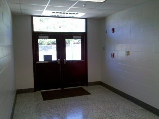 Short corridor to the rear entrance between Rooms 27 (right) and 28 (left). This small hallway was normally not used by students except during fire drills, but did see heavy use by staff due to the location of a small staff parking lot just beyond these doors.
