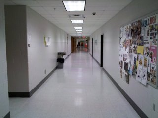 Social studies hallway. The photo at left shows the intersection of the rear hallway with the main social studies hallway, and the photo at right is the main social studies hallway looking all the way up to the front of the building where the foreign language classrooms are located. Compare this to a similar view in 2001, before renovations. The classroom door seen in the left photo is Room 65, former Room 30, which was Coach Parks' classroom.