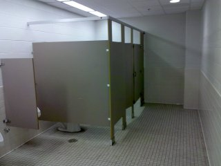 Men's restroom across from where Guidance used to be. I want the male alumni to notice: high partitions and doors on the stalls! During my time as a student, there were no doors on the stalls in the men's restroom, and based on the old stall partition design, they were never intended to have doors on them. Now they have corrected that problem with the renovation, giving male students the privacy in the restroom that they were always entitled to but never got.
