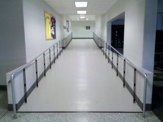 The entrance to the cafeteria has been reconfigured to make it more accessible. Originally, this area contained the entrance to the teachers' lounge, a set of restrooms, and a small flight of steps down to the cafeteria, which was at a lower level than the rest of the school. Now, the entrance to the teachers' lounge has been relocated to around the corner, the restrooms were completely reconfigured to face the home economics/music hallway, and the stairs have been replaced with a long ramp. This also eliminated the need for the wheelchair lift that was accessed through the teachers' lounge.