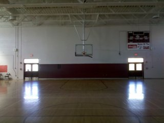 """The original gym, now one of two gymnasiums at SDHS, looks mostly the same as it always did. Aside from new paint and a refinished floor, the only major change to the gym was the replacement of the bleachers with new ones that had """"SDHS"""" written on them in large letters. However, what struck me most when going in here was how bare the space now looked. When I attended school here in the late 1990s, the walls were covered with banners and signs touting various athletic championships, and there was a large cougar mural on the rear wall. The mural has been painted out, and the banners and such were relocated to the new gym."""