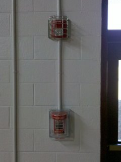 The new fire alarms in the gym received typical treatment for fire alarm equipment installed in gymnasiums, where there is a higher likelihood of the equipment's being struck by objects. The new horn/strobes are in cages, and the new pull stations have Stopper covers on them. The Stopper covers are particularly important, as I remember an accidental alarm that happened during my senior year, caused by a basketball's striking a pull station in the gym.