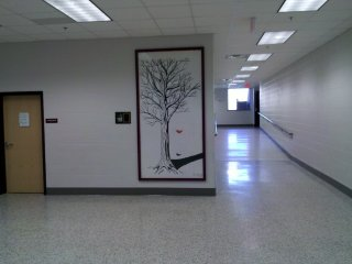 Outside of the entrance to the new gym is the only remaining artwork from prior to the renovation: a painting of a tree by David Branch, a 1996 graduate. This painting was previously located in the auditorium.