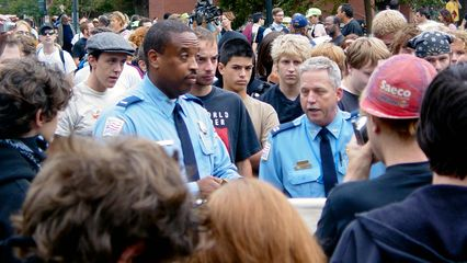 The two uniformed officers, primarily the officer to the right in this photo, explain what's going on.