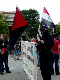 A group of people carried a banner with the URL for hacktivist.net, while also flying the Iraqi flag, as well as the red-and-black anarcho-syndicalist flag.