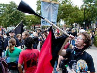 A man blows on a horn with the anarcho-syndicalist flag hanging from its shaft.