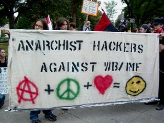 Another group carries a banner similar to that of the Hacktivist group.