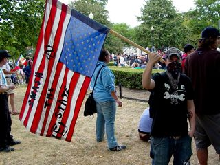 """Black bloc demonstrators' statements took various forms. The gentleman on the left carries a flag, flown upside down (an international distress signal), with """"smash the state"""" written on it. Another gentleman is dressed for battle, wearing a helmet, goggles, padding on both arms, and carrying an anarchist flag."""
