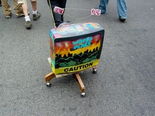 Meanwhile, a person drags a television on wheels, creatively painted up and wrapped in caution tape.