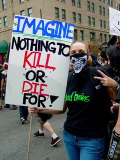 """A woman wearing a bandanna with part of a skull printed on it carries a sign saying, """"Imagine nothing to kill or die for!"""""""