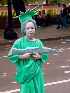 A girl dressed as the Statue of Liberty carries a toy machine gun.