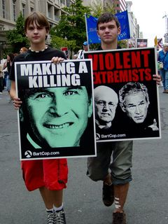 Two people hold up signs indicating who they perceive the real terrorists to be...