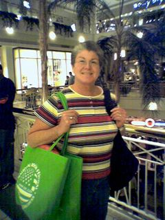 Mom poses for a photo at Pentagon City, carrying a bunch of stuff that she got from the National Book Festival.