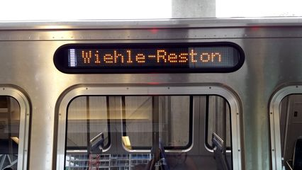 """Car 7000, displaying """"Wiehle-Reston"""" with color swatch. Due to technical limitations on the existing fleet's signs, the existing revenue fleet would not display any color swatch for Silver Line service."""