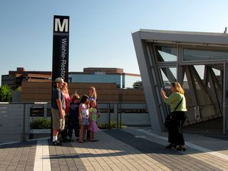 A family poses for a photo in front of the pylon at Wiehle-Reston East.