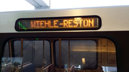 """Train at the platform at Wiehle-Reston East with """"WIEHLE-RESTON"""" destination sign."""