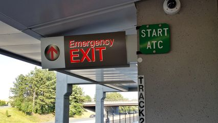 Emergency exit and automatic train control signage at the inbound end of the platform.