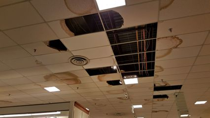 These photos, taken on March 30, 2016, show the poor state of the roof over the JCPenney building from inside. There were many leaks in the roof, with lots of missing and damaged ceiling tiles bearing this out.