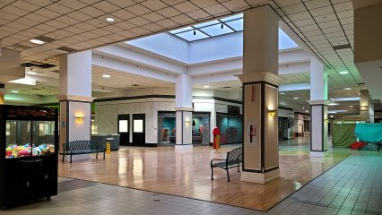 The center court. The center court originally contained a large fountain under the skylight that sprayed a mist. The fountain was removed during the buildout for Stone & Thomas and replaced by the wood laminate flooring that is there now.