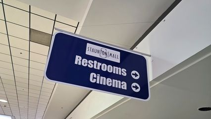 """Colonial-era signage directing patrons to the mall restrooms and the movie theater. The """"Staunton Mall"""" logo covers the original Colonial Properties Trust logo, which resembled a shooting star."""