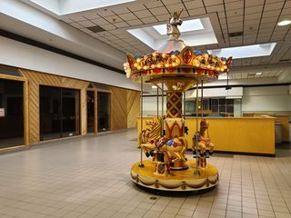 Coin-operated children's carousel, located behind the play area.