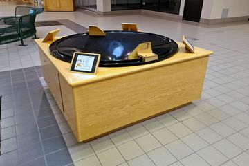 """""""Wishing Well Coin Race"""" in the Belk wing. This was a device where you put a coin in a slot at the top, and then the coin rolled in circles before eventually falling into the hole in the middle."""