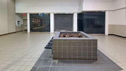 Northernmost store space on the east side of the Belk wing. This space was originally occupied by Holliday's Shoe Store, but it was vacant by the time that I became familiar with the mall in 1992. The space was briefly used in the late 1990s to store the fixtures for Payless ShoeSource after they closed and vacated their space in the JCPenney wing, and it was later used for a kiddie gymnastics facility in the 2000s.