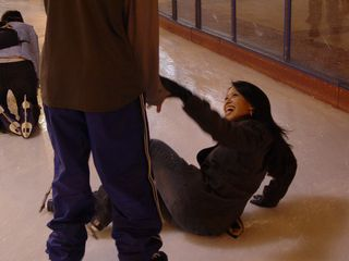At Pentagon Row, a man helps a woman up after she took a spill on the ice.