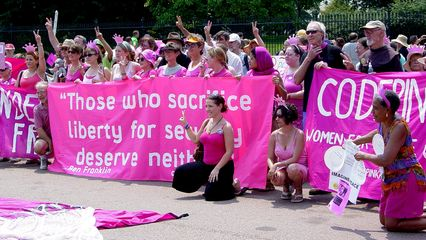 """On July 4, Code Pink held a large demonstration in the street in front of the White House. Here, they gave Bush a giant """"pink slip"""", which you can partly see in the bottom photo."""