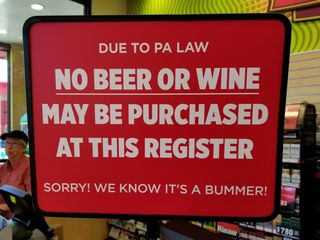 Signs advising patrons of a requirement that fuel and alcoholic beverages must be purchased at separate registers.