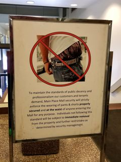 """Behavioral signs in the mall. One sign bans the wearing of pants lower than the waist (i.e. no """"droopy drawers""""), and the other bans the playing of audible music."""