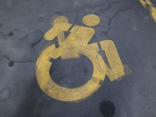 I spotted this in the garage where we parked the car. Someone painted the new wheelchair symbol over the old wheelchair symbol.