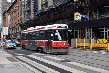 """A streetcar, doing the 501 to Humber, passes by the store. Jodie boarded 4016, another CLRV, just up the street from this location in """"Our Story Part 2""""."""