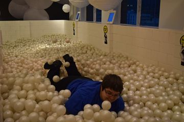 Elyse plays in the ball pit.