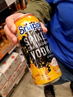 Elyse shows off a can of Snapple Spiked Peach Tea Vodka.