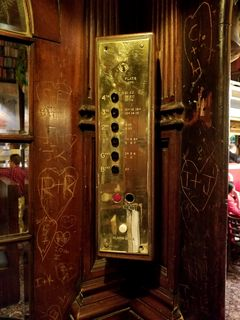 The button panel on the elevator car. Unfortunately, many patrons before us had carved their initials and such into the woodwork.