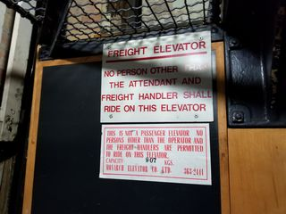 Signage inside the elevator about its being a freight elevator, and listing maximum capacity of 907 kg (approximately 2000 lbs).