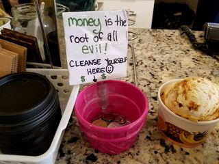 """Sign on the tip jar reading, """"Money is the root of all evil! Cleanse yourself here."""""""