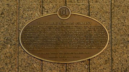 """The plaque, at the entrance to the Queen subway station on the north side of the store. This is the plaque that the one in """"Our Story"""" was based on. This is now one of two historical markers on the building."""
