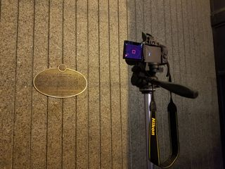 """A """"meta"""" photo of sorts, showing a photo of the taking of a photo of the plaque."""